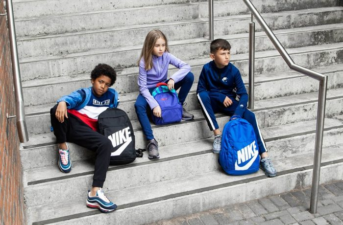 Children with Nike backpacks sitting on stairs